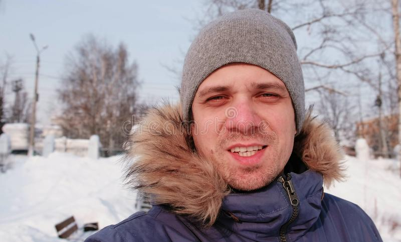 Portret zima młody człowiek patrzeje kamerę w popielatej nakrętce i błękita puszka kurtce obraz royalty free
