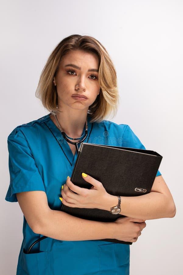 Portret zmęczeni kobiety lekarki mienia dokumenty i oddychanie za fotografia stock