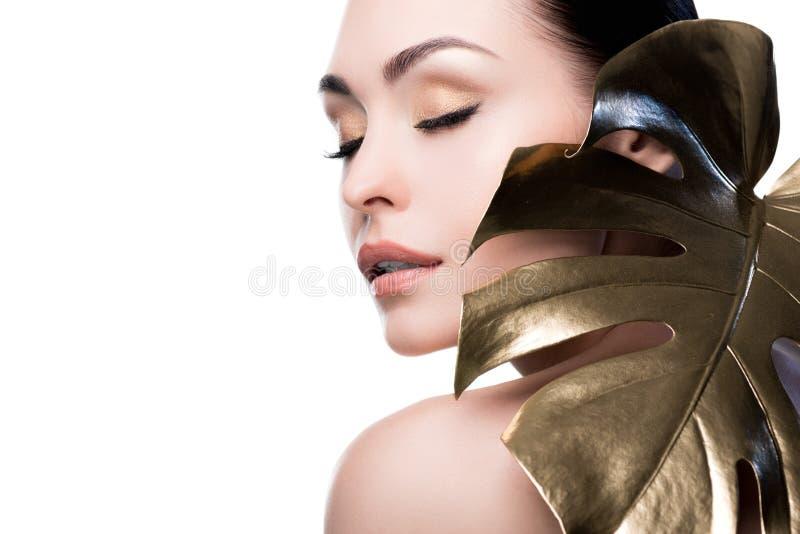 Portret zmysłowa kobieta z dużego złotego liścia pobliską twarzą fotografia stock