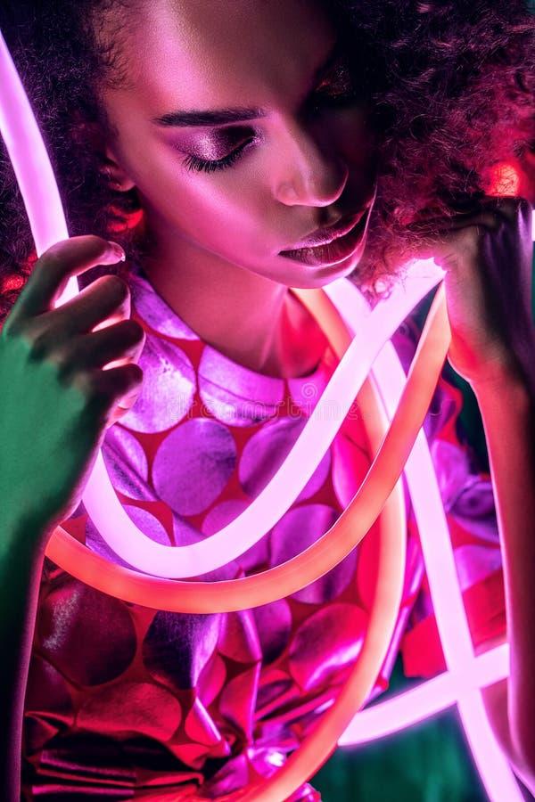 Portret zmysłowej kobiety afrykańskiej z różowym neonem w pobliżu twarzy zdjęcia royalty free