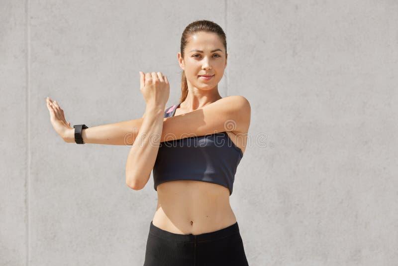 Portret zrelaksowana młoda piękna sporty kobieta rozgrzewkowa w górę trenować przed, patrzejący bezpośrednio przy kamerą, jest ub zdjęcia stock