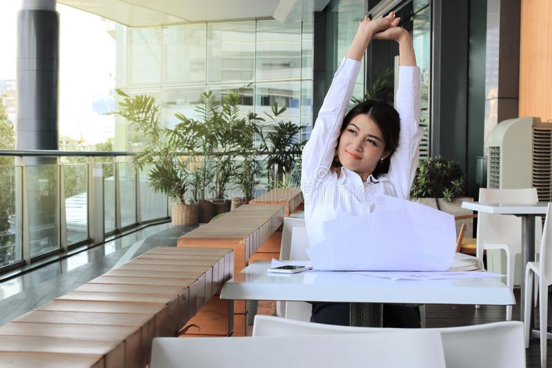 Portret zrelaksowany młody Azjatycki biznesowej kobiety obsiadanie i dźwiganie ręki zasięrzutne w biurze zdjęcie stock