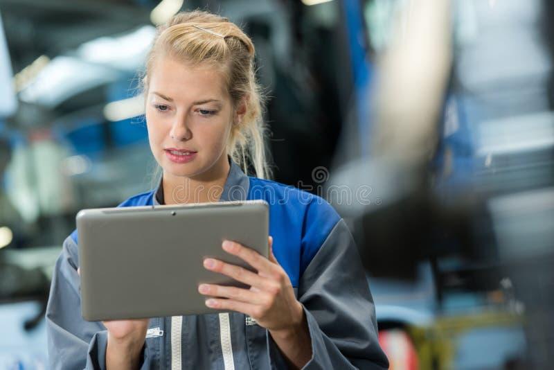 Portreta żeński pracownik fabryczny używa cyfrową pastylkę zdjęcia royalty free