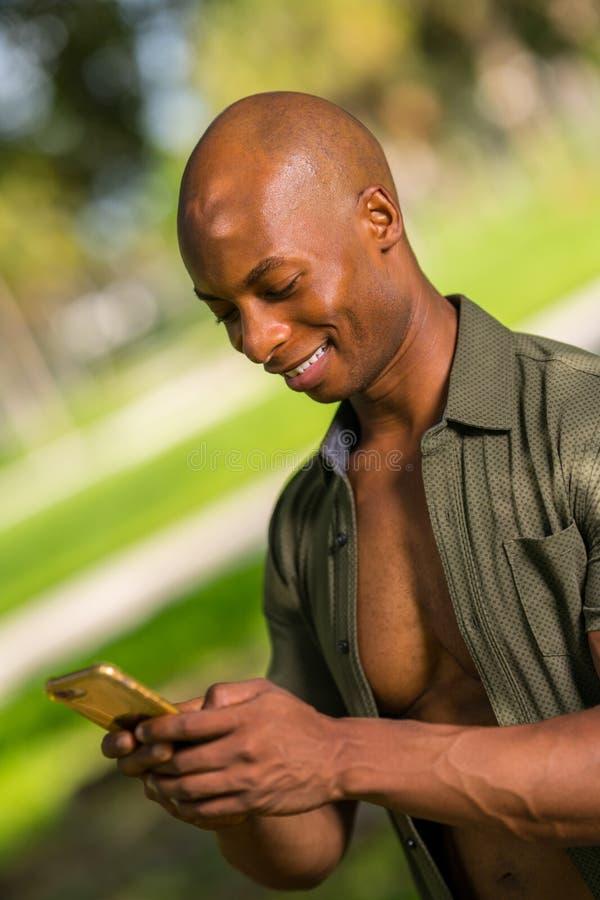 Portreta amerykanin afrykańskiego pochodzenia przystojny młody mężczyzna uśmiecha się wiadomość tekstową na jego smartphone i wys obraz royalty free