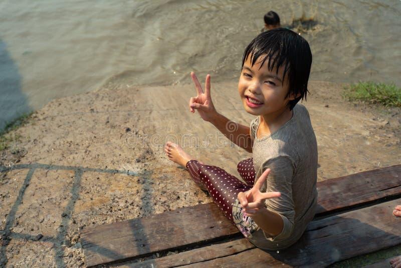 Portreta azjaty mokra dziewczyna cieszy się sztuki suwak w borowinowym stawie w gospodarstwie rolnym zdjęcia royalty free