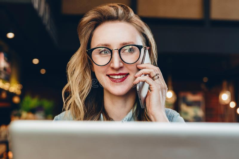 Portreta bizneswoman siedzi w kawiarni przed laptopem w szkłach, opowiada na telefonie Dziewczyny blogger komunikuje telefonem zdjęcie stock