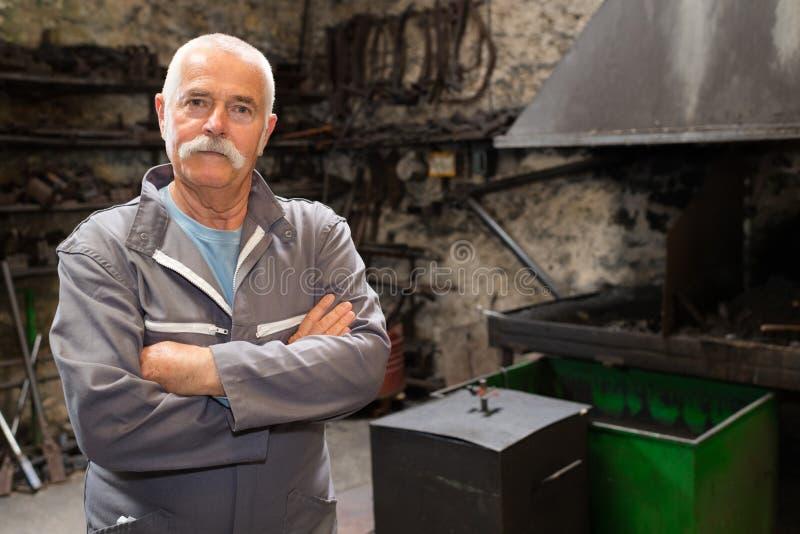 Portreta blacksmith ufna pozycja kuźnią w warsztacie obraz stock