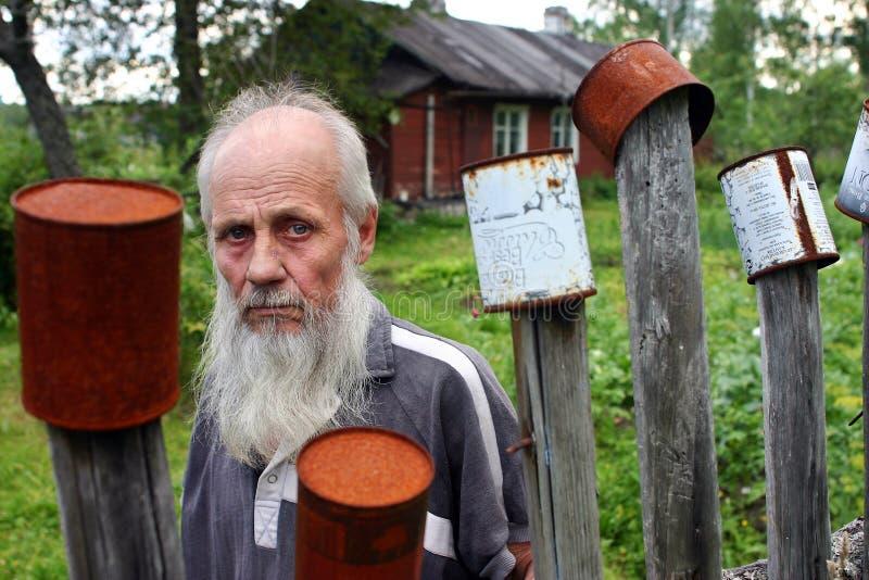Portreta brodaty stary człowiek na tło drewnianym domu wiejskim. fotografia royalty free