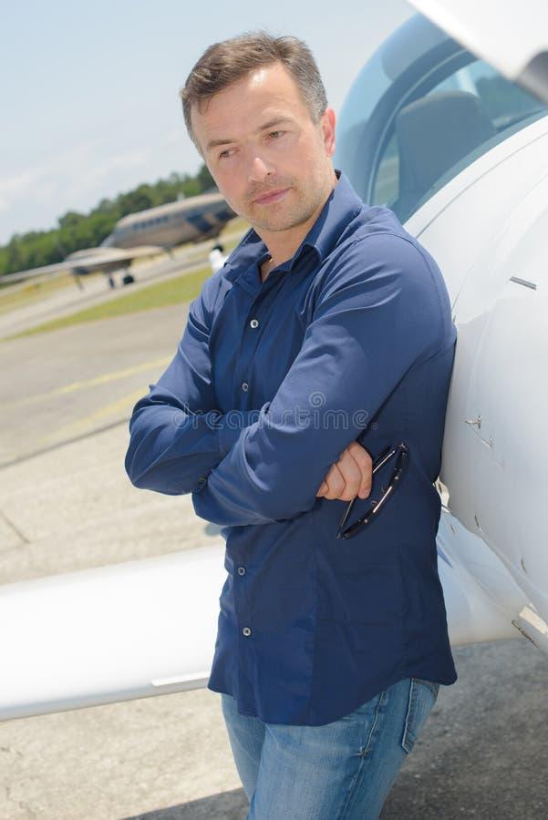Portreta dorosłego pilota chłodno młody obsiadanie przeciw intymnemu samolotowi fotografia royalty free