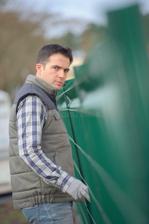 Portreta mężczyzna wyprostowywa ogródu ogrodzenie zdjęcia royalty free