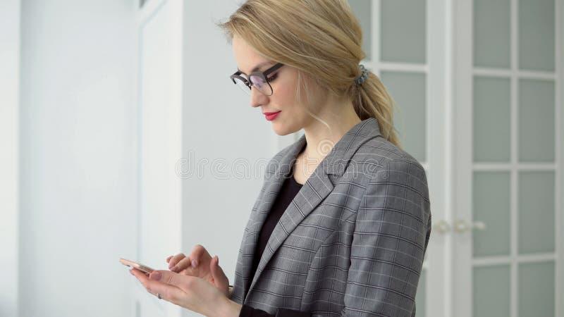 Portreta młody bizneswoman używa smartphone mienia mobilnego gadżet i texting wiadomość, dziewczyna uśmiech obraz royalty free