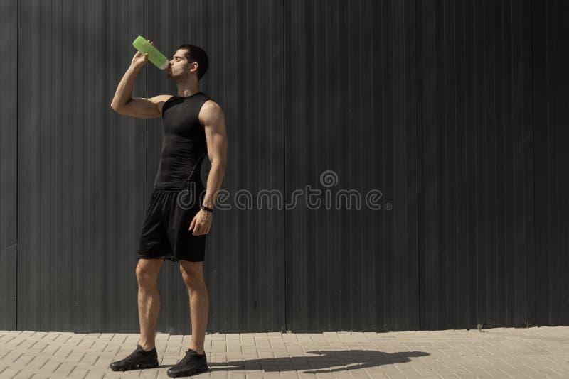 Portreta mięśniowy mężczyzna bierze przerwę nawadniać jego ciało póżniej obraz stock