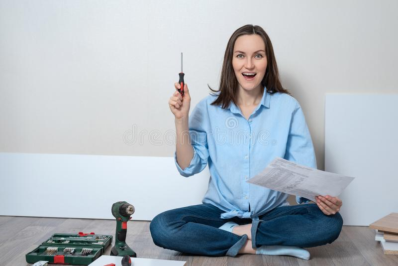 Portreta ofyoung uśmiechniętej kobiety siedzący onfloor z śrubokrętu i meble zgromadzenie instrukcjami, kopii przestrzeń obraz royalty free