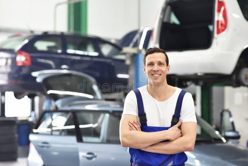 Portreta pracownik, mechanik w garażu/- uśmiechnięty mężczyzna w workwear obrazy stock