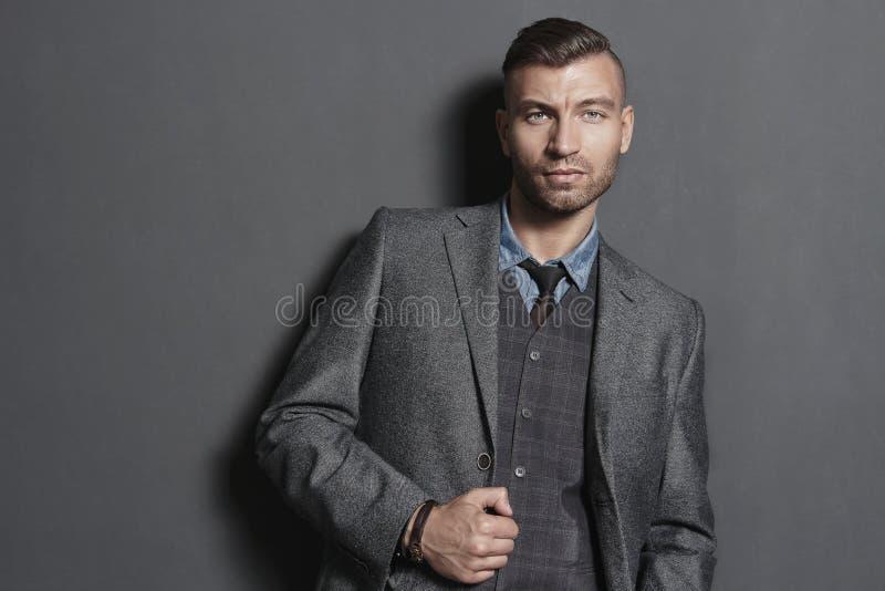 Portreta przystojny modny mężczyzna w kostiumu przeciw szarości ścianie obrazy royalty free