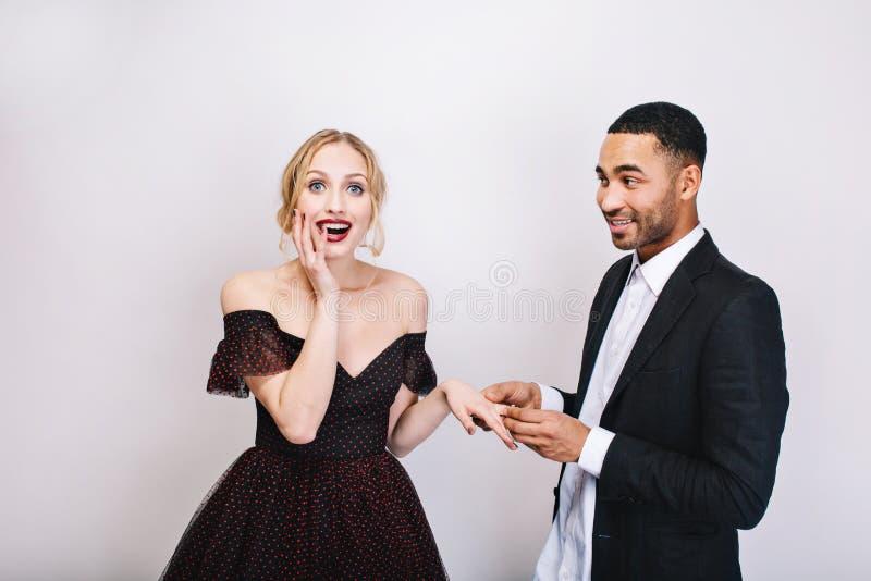 Portreta przystojny radosny mężczyzna w białej koszulowej robi propozycji małżeństwo atrakcyjna zdumiewająca młoda kobieta w luks fotografia stock