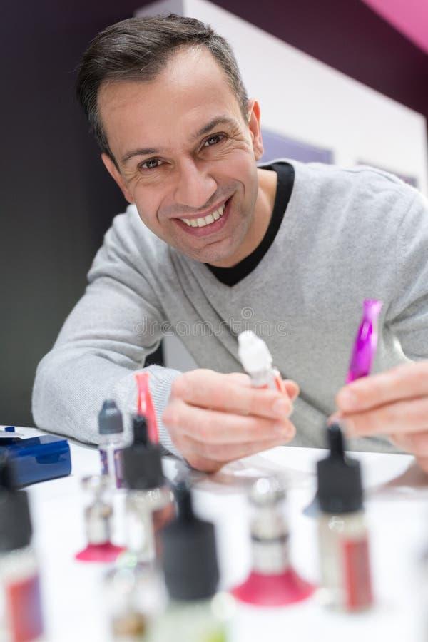 Portreta sprzedawcy mienia odparowalnika uśmiechnięty ciecz obraz stock