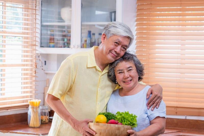 Portreta szczęścia azjatykcia starsza para przy kuchnią z pucharem świeża sałatka i patrzeć kamerę, starzeje się w domu  fotografia royalty free