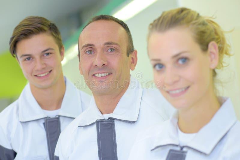 Portreta trzy pracownicy w dopasowywanie mundurach fotografia stock