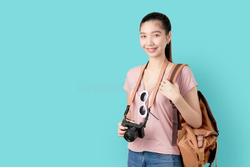 Portreta uśmiechu szczęśliwie Azjatycka kobieta gotowa podróżować, turystyka i wakacje z plecakiem, fotografii kamera na błękitny obrazy royalty free
