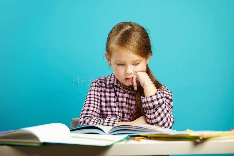 Portreta ucznia zadumany obsiadanie przy stołem z udziałem książki i fascynujący czytanie na odosobnionym błękicie Uczennica obrazy royalty free
