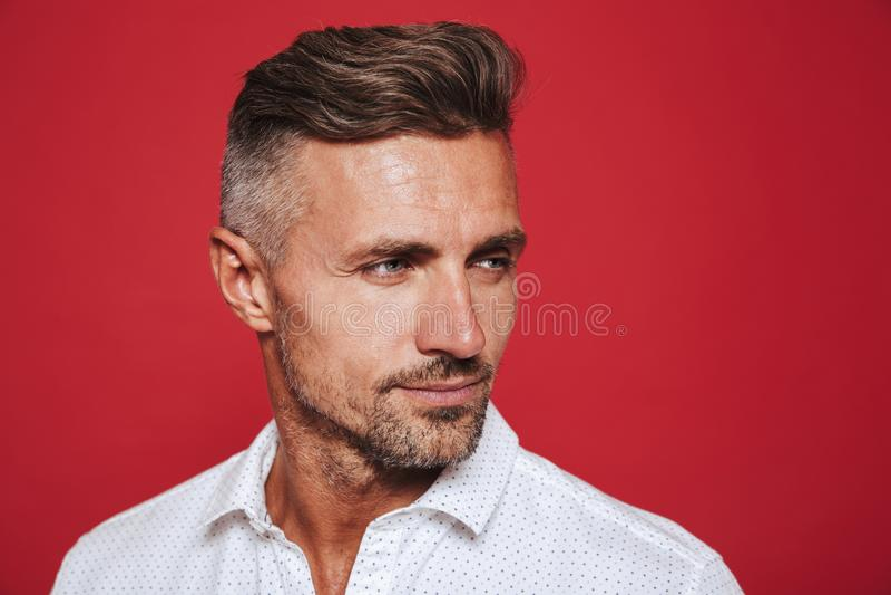Portreta zbliżenie dorosły mężczyzna 30s w biały koszulowy patrzeć na boku, obrazy royalty free