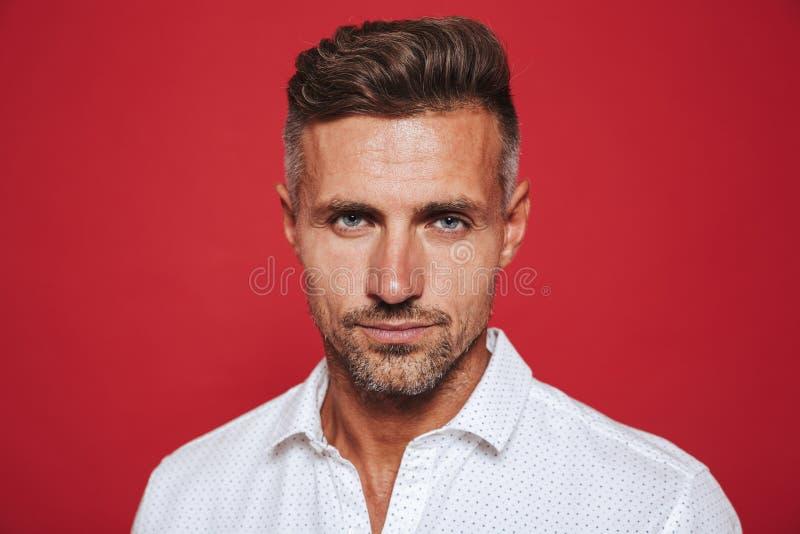 Portreta zbliżenie zarośnięty mężczyzna 30s w białym koszulowym patrzeje c fotografia royalty free