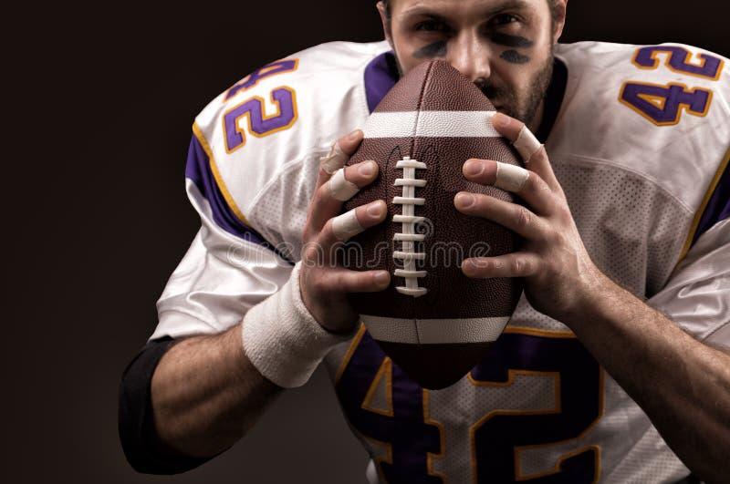 Portretclose-up, Amerikaanse voetbalster, gebaard zonder een helm met de bal in zijn handen Concept Amerikaan royalty-vrije stock fotografie