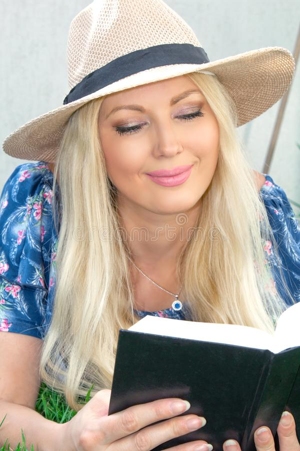 portretclose-up De mooie blonde jonge vrouw in een hoed ligt op het gras en leest een boek stock foto