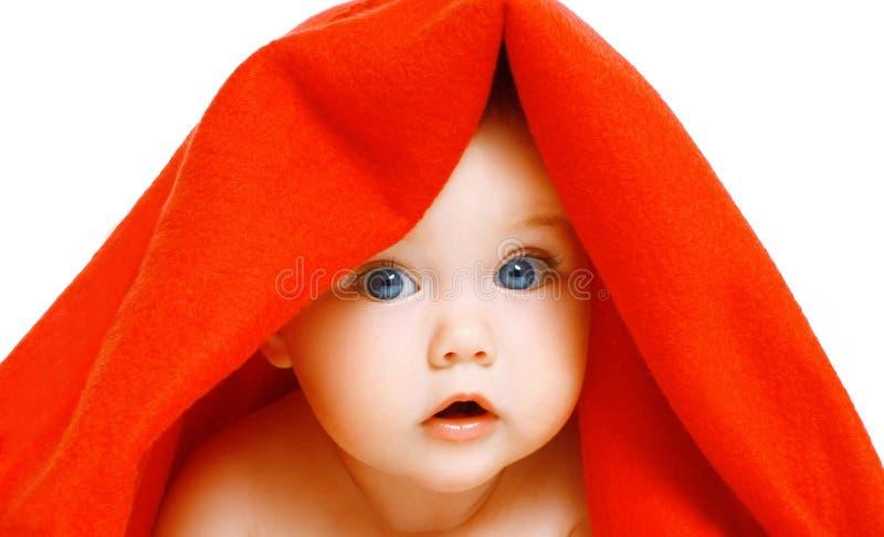 Portretclose-up van gezichts leuke baby onder rode handdoek op een wit stock fotografie