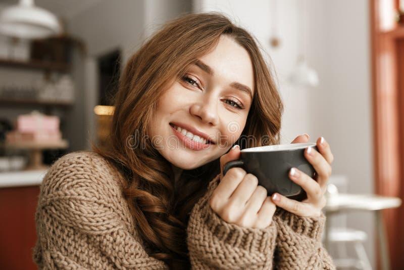 Portretclose-up van tevreden vrouw in gebreide sweater, het zitten stock afbeelding