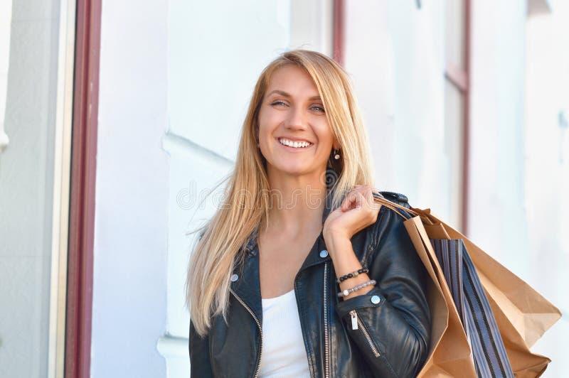 Portretjongelui die langharige vrouwenholding het winkelen zakken charmeren stock fotografie