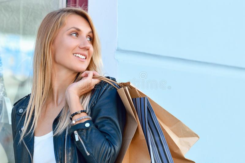 Portretjongelui die langharige vrouwenholding het winkelen zakken charmeren royalty-vrije stock afbeelding