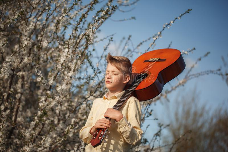 Portretjongen met gitaar die zich dichtbij bloeiende bloemen in de zomerdag bevinden royalty-vrije stock foto's