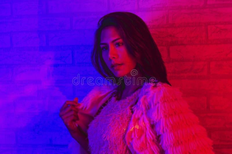 Portretmanier van een Aziatische vrouw in neon-viooltje en rood licht dat in dark met schoonheid en sexy glanst, verleidelijk, he royalty-vrije stock foto