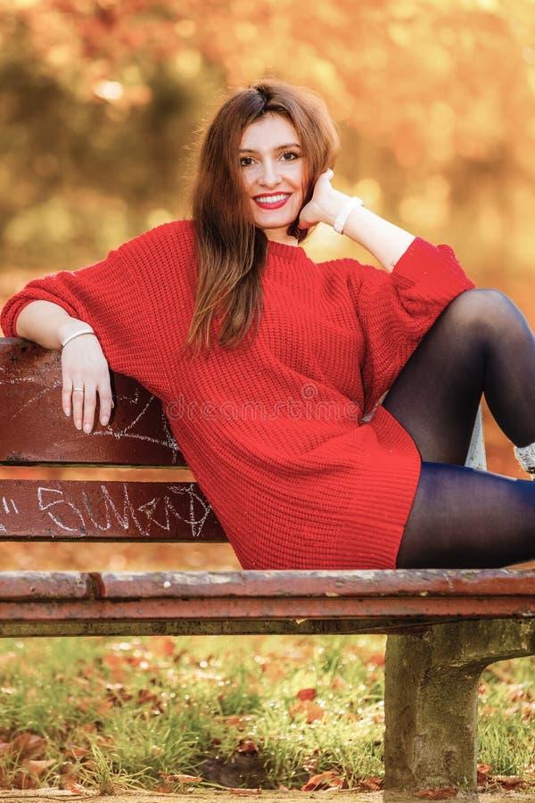 Portretmeisje het ontspannen op bank in herfstpark royalty-vrije stock afbeeldingen