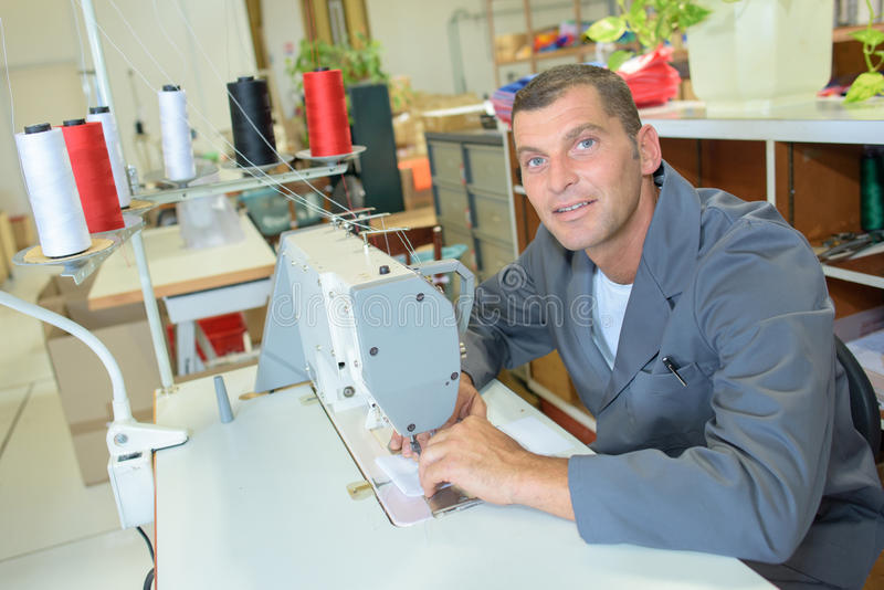 Portretmens bij naaimachine wordt gezeten die royalty-vrije stock foto's