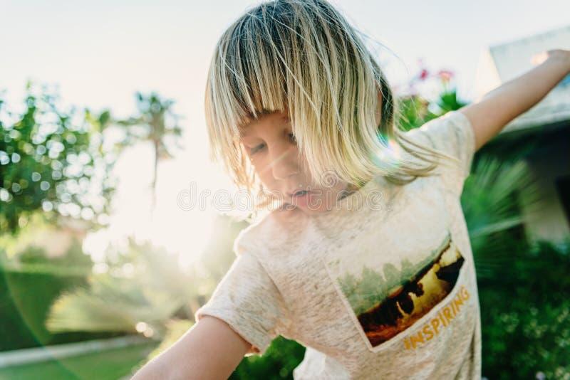 Portretowy blond chłopiec, 5 lat prostych włosów, grający na podwórku, walcząc na łyżwach, rozkwita słońce obraz stock