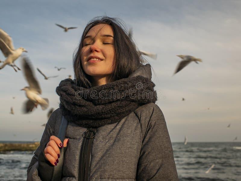 Portretten jong aantrekkelijk meisje op de achtergrond van het overzees, de hemel en de meeuwen royalty-vrije stock afbeeldingen