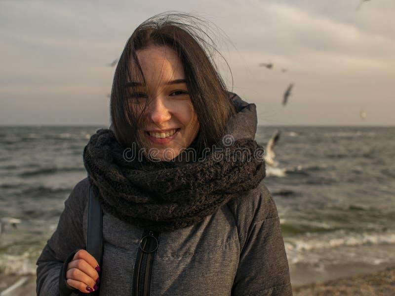 Portretten jong aantrekkelijk meisje op de achtergrond van het overzees, de hemel en de meeuwen royalty-vrije stock afbeelding