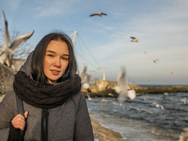 Portretten jong aantrekkelijk meisje op de achtergrond van het overzees, de hemel en de meeuwen royalty-vrije stock foto's