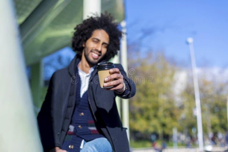 Portretten van een Knappe en modieuze afro het glimlachen mensenzitting in openlucht en het tonen bij camerakop van koffie Gelukk royalty-vrije stock afbeelding