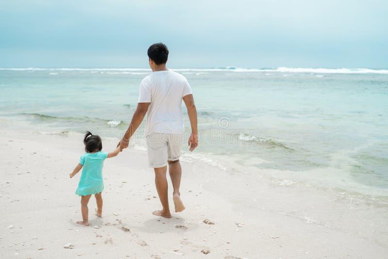 Portretvader en dochter die samen rond het strand met greephanden lopen royalty-vrije stock afbeeldingen