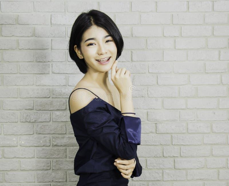 Portretvrouw van zwarte kortharig in luxueuze blauwe kleding, bakstenen muurachtergrond met helder en leuk concept Aziatische mei royalty-vrije stock afbeeldingen