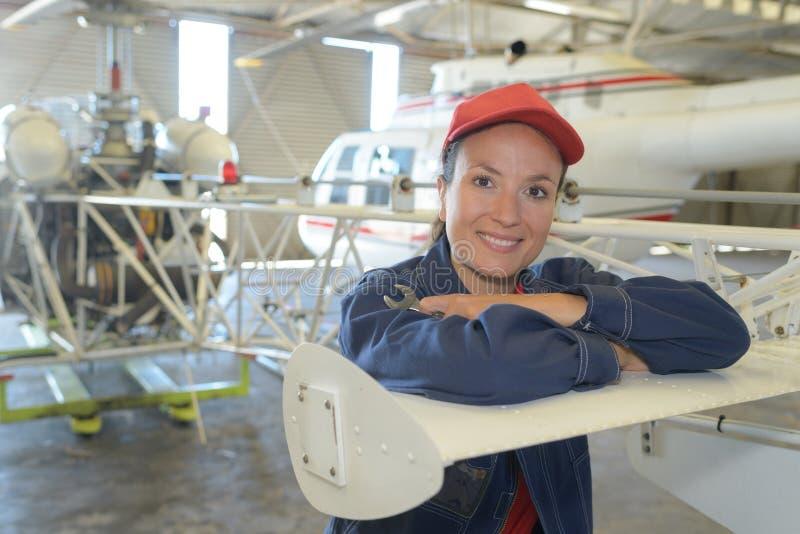 Portretvrouw in vliegtuigenhangaar stock afbeeldingen