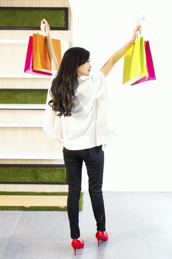 Portretvrouw in zwart-witte kostuum holding gekleurde het winkelen zakken en creditcard Meisje die glimlachend en gelukkig kijken stock afbeelding