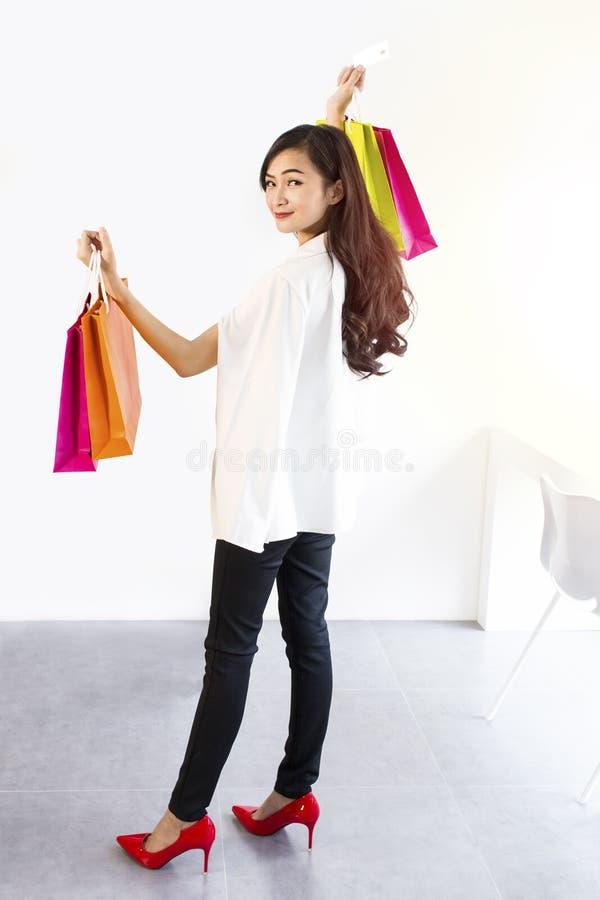 Portretvrouw in zwart-witte kostuum holding gekleurde het winkelen zakken en creditcard Meisje die glimlachend en gelukkig kijken royalty-vrije stock afbeelding