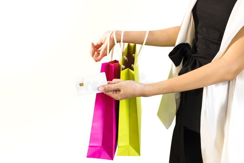 Portretvrouw in zwart-witte kostuum holding gekleurde het winkelen zakken en creditcard Meisje die glimlachend en gelukkig kijken stock foto