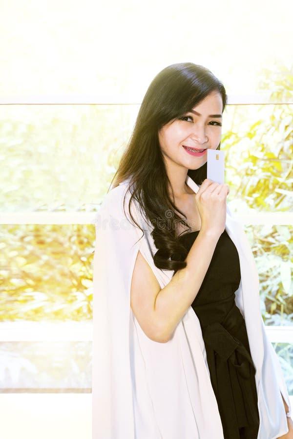 Portretvrouw in zwart-witte kostuum holding gekleurde het winkelen zakken en creditcard Meisje die glimlachend en gelukkig kijken stock fotografie