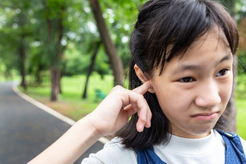 Portrety małej, azjatyckiej dziewczynki zestresowane wbijaniem palca do ucha, denerwowanym wyrazem, zamknięciem uroczego dziecka, obraz stock